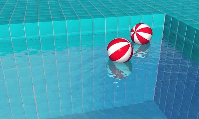 dva červenobílé míče na hladině bazénu